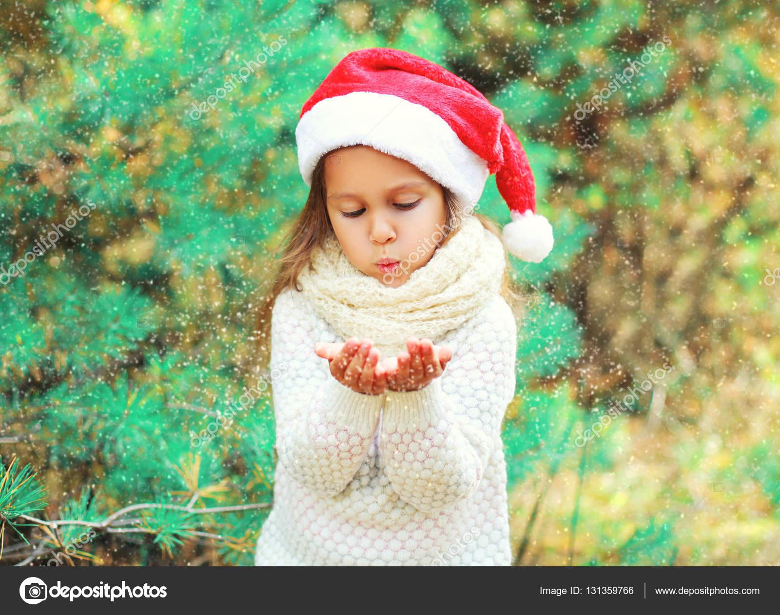 Niño de Navidad niña sombrero rojo de santa nieve miente en sus manos sobre  un árbol — Foto de Rohappy e2ef79683c8