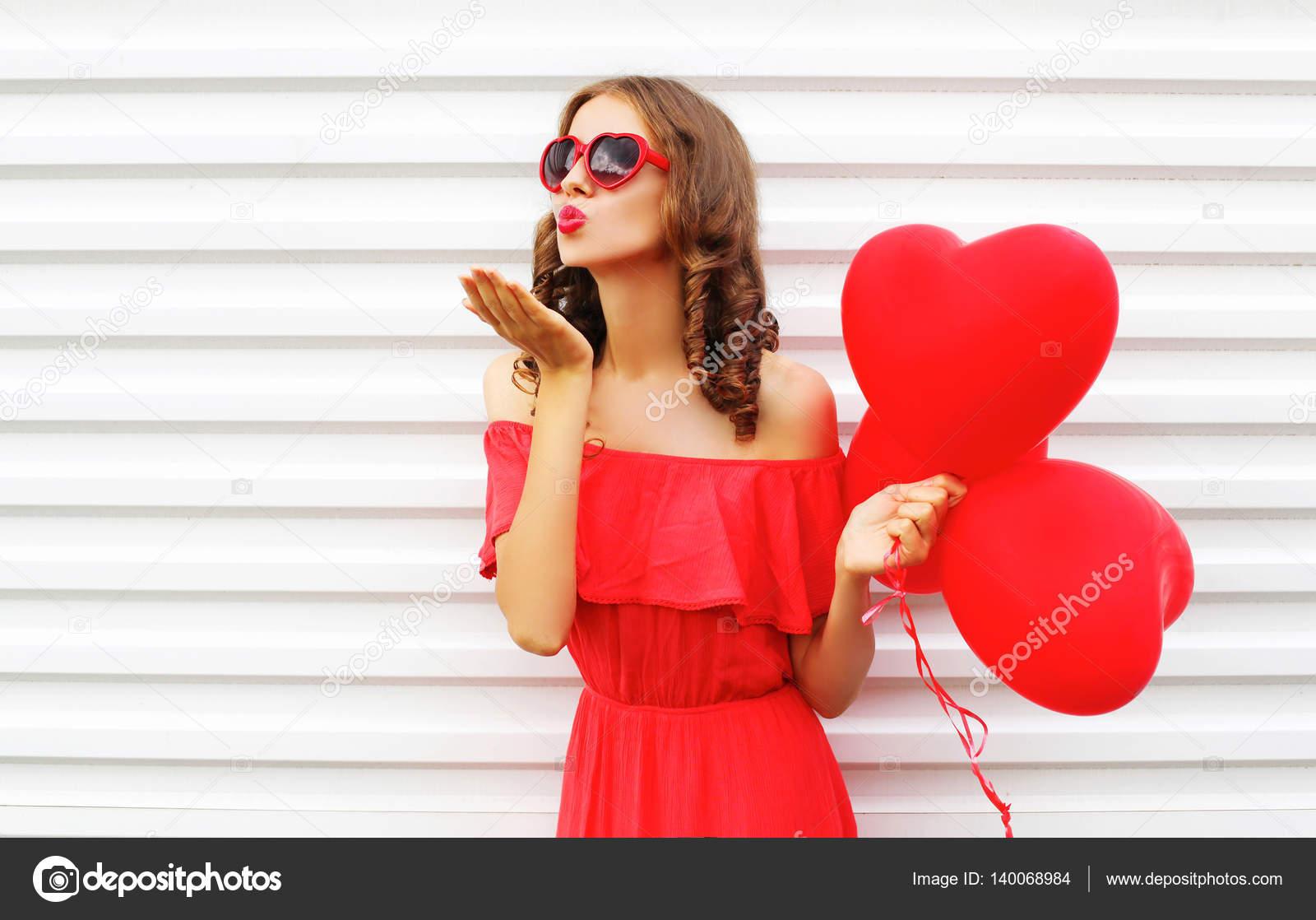 Porträt Frau im roten Kleid sendet Luft Kuss mit Ballon Herz