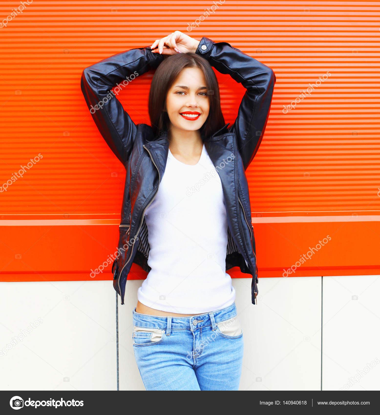 Lächelnde junge Frau im weißen Hemd, schwarzer Lederhose und