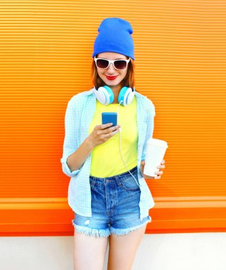 Fashion smiling young woman using smartphone with a coffee cup o