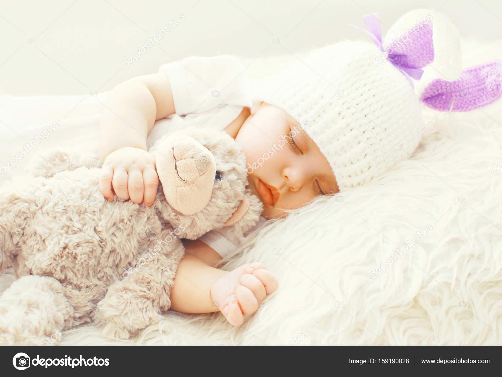 Lindo bebé durmiendo con el osito de peluche en una cama suave ...