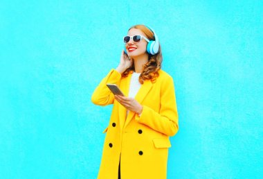 Fashion pretty smiling woman with smartphone listens to music in