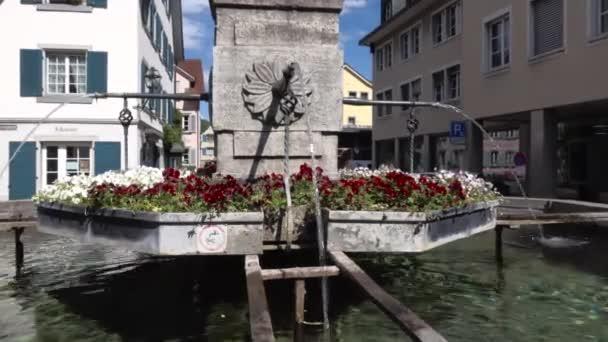 BULACH, SWITZERLAND - Április 27, 2020: Festői régi szökőkút díszítő virágokkal az óvárosban. Hagyományos svájci fapados házakkal körülvéve. Lövés közeledik..