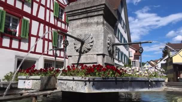 BULACH, SWITZERLAND - Április 27, 2020: Festői régi szökőkút díszítő virágokkal az óvárosban. Hagyományos svájci fapados házakkal körülvéve. Közelkép, parallax felvétel..