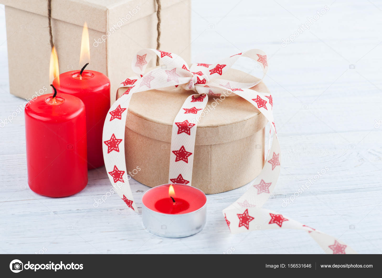 gift in kraft box with red stars ribbon lit candles and heart