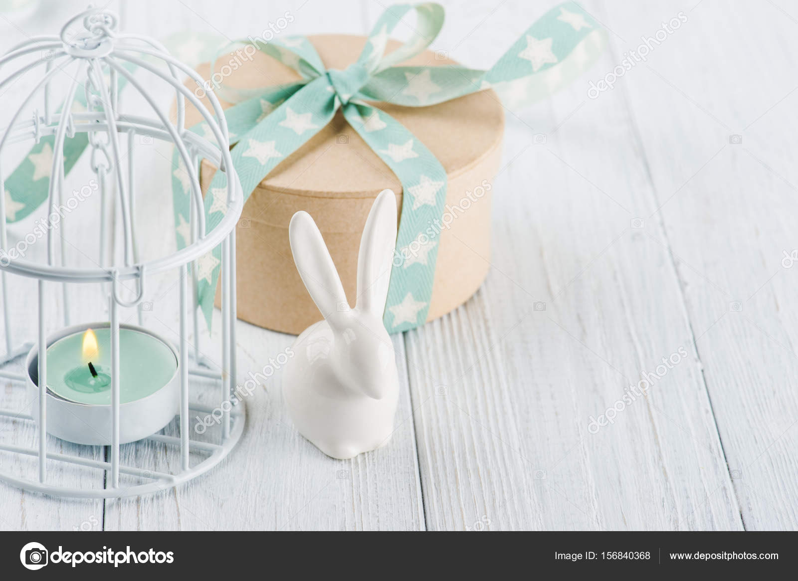 Mint green lit candle in white lantern with gift — Stock Photo ...