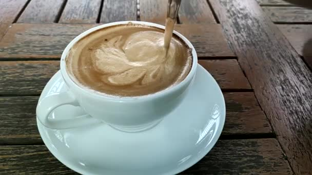 Supper slow motion of hot cappuccino with nice milk pattern with coffee bean