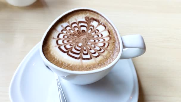 hot cappuccino coffee with nice pattern foam on table