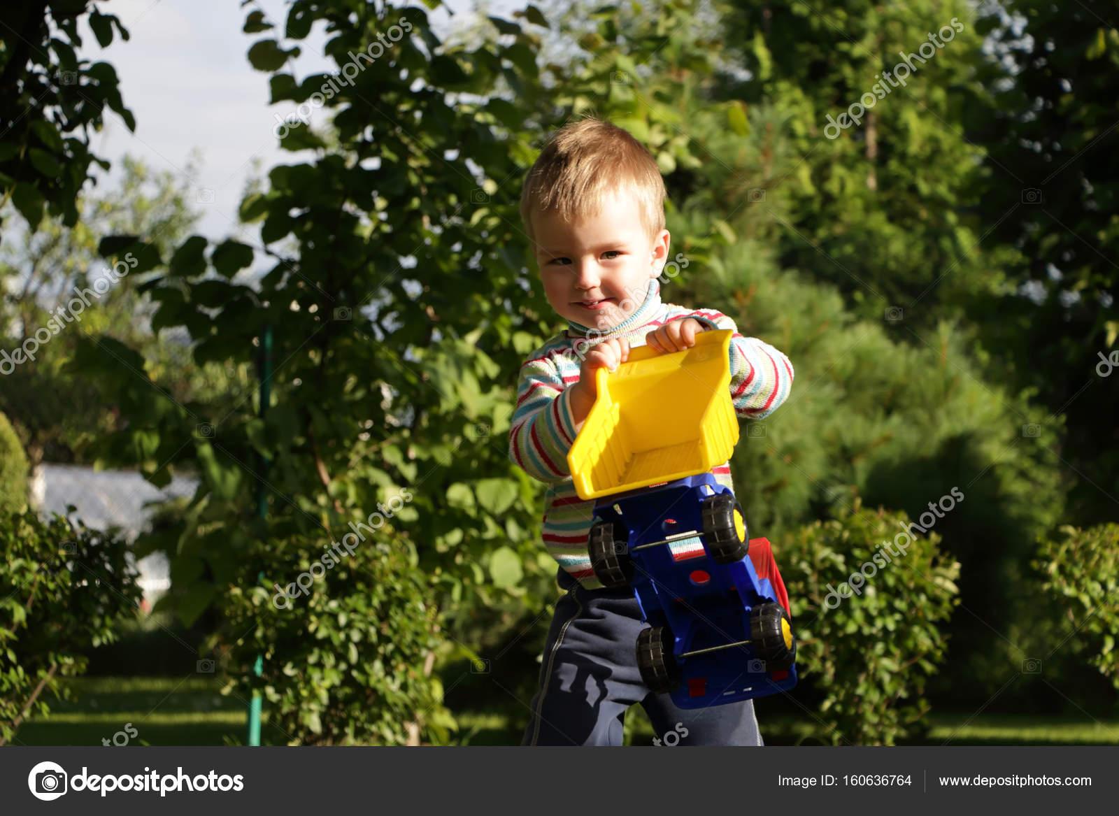 ein junge spielt in einem kinderspielzeug auto im garten — stockfoto