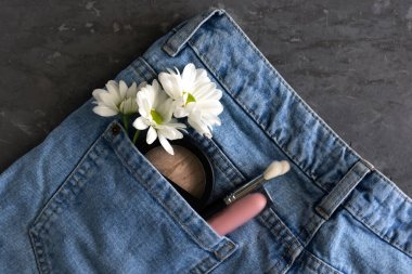 cosmetics in the pocket of trousers, beauty concept, decorative cosmetics close-up, flat la