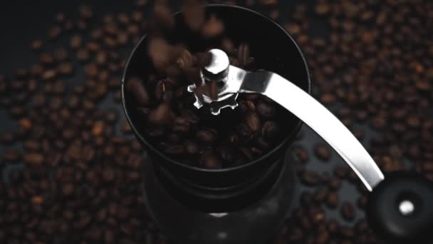 Fried coffee beans are falling to the manual grinder. Cinematic slow motion video. Preparation of fresh beverage morning coffee for breakfast. Mill for grinding. Isolated on black background.