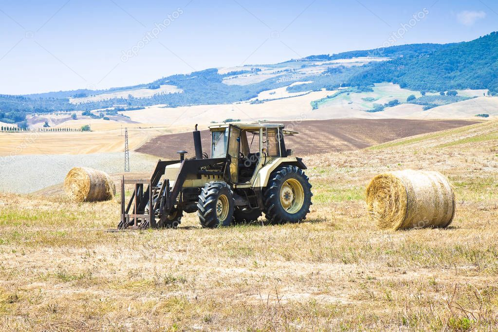 Old tractor stopped in a hill with round bales on background