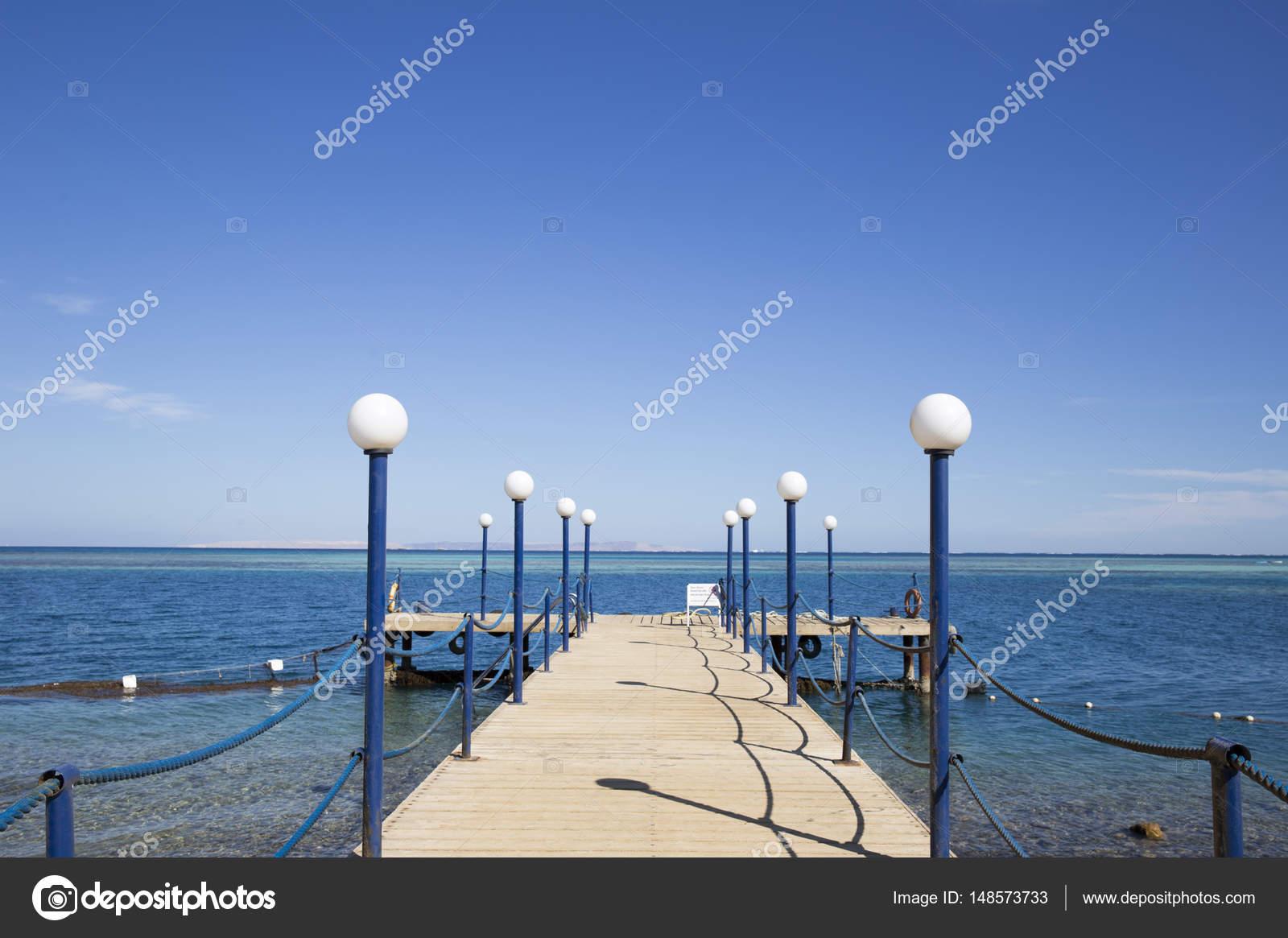 Pilastro di legno con luci di via recintato con corde di ferro sul