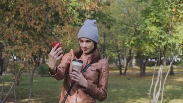 Fiatal lány vesz egy selfie a háttérben a falra, szép őszi levelekkel.