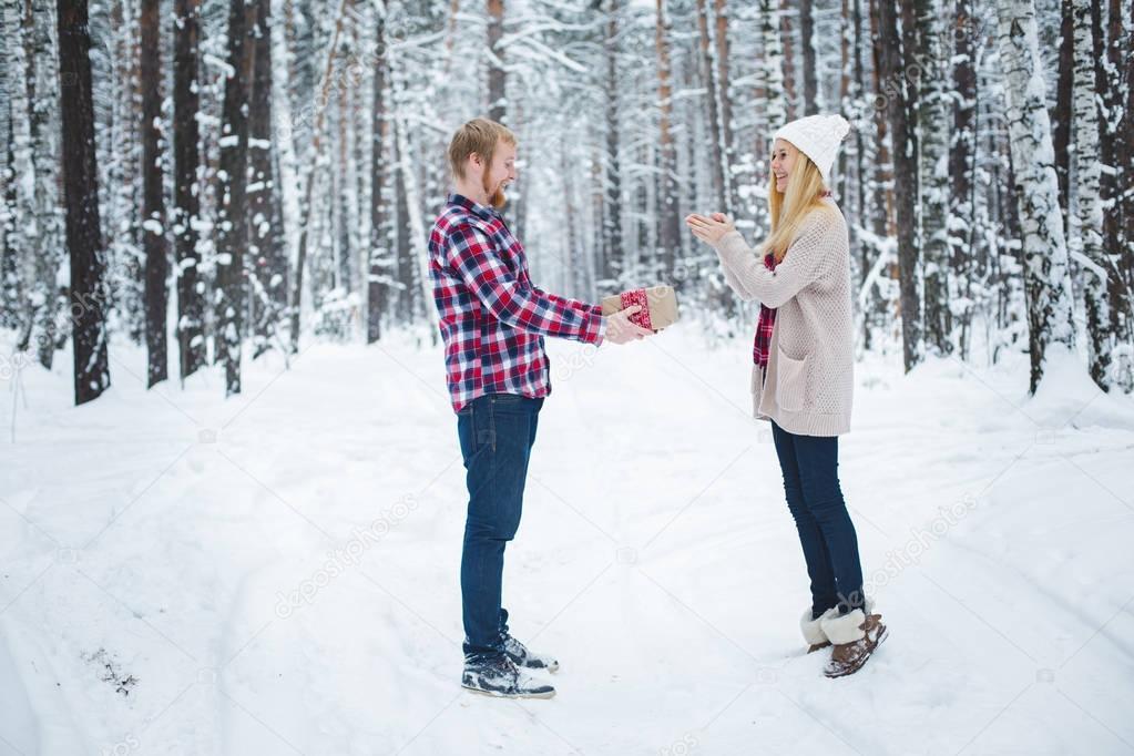 junger Mann präsentiert Frauen Weihnachtsgeschenk im Wald ...