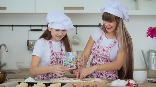 Matka a dcera v kloboucích a zástěry, koláčky pečte vánoční