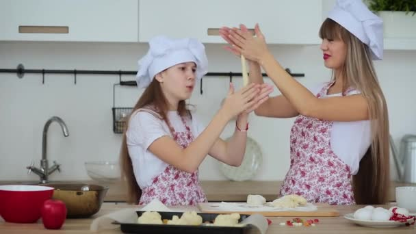 Mother and daughter in hats and aprons to cook scones for Christmas
