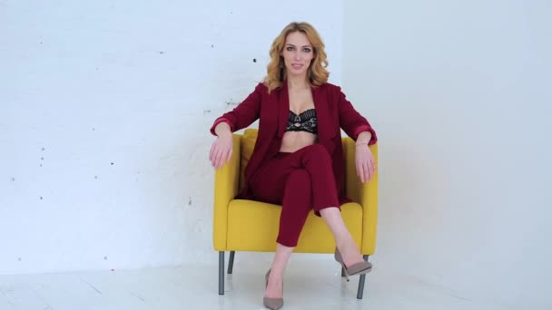 beautiful sexy woman in red suit on a yellow chair