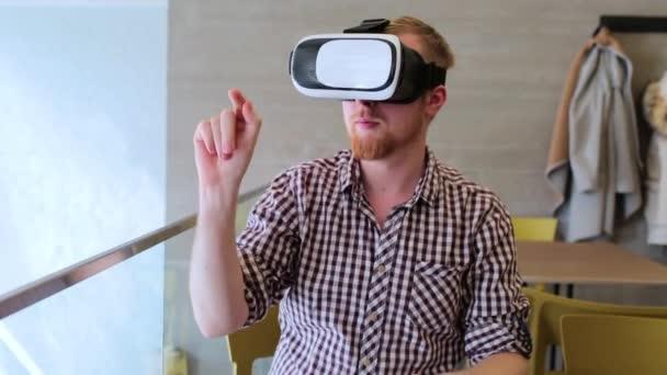 ein bärtiger Mann mit Virtual-Reality-Brille im Café