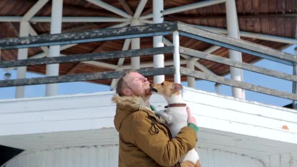 man throws dog Jack Russell in the background of the lighthouse