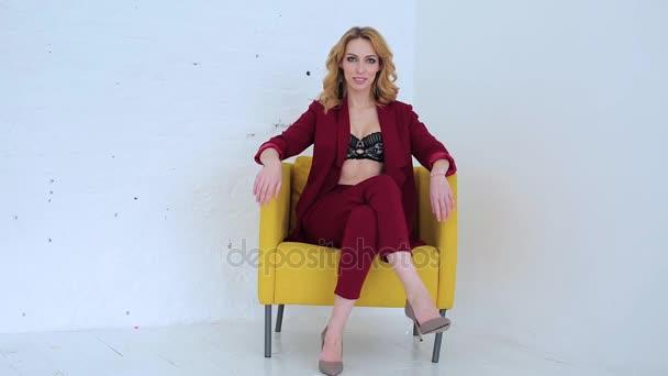 Krásná sexy žena v červeném obleku na žluté židle