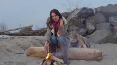 Young woman sitting near the fire in the evening. fire.