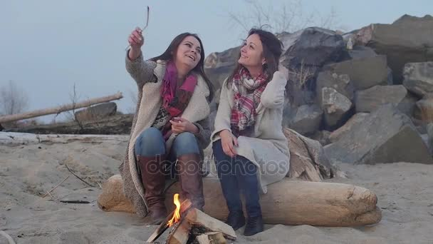 dvě ženy, posezení u ohně. Piknikový gril