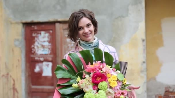 Beautiful young woman in a coat with a bouquet of flowers