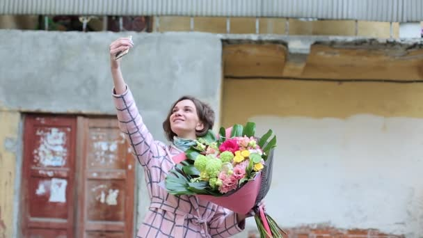 woman in a coat with a bouquet of flowers is photographed on the phone