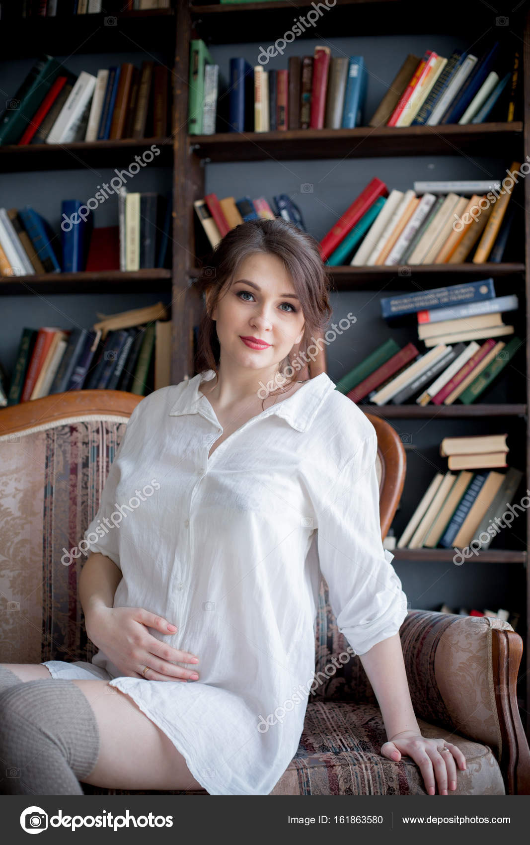 37000cb83 Retrato de una joven embarazada en camisa blanca en el estudio en una silla  — Foto de ...