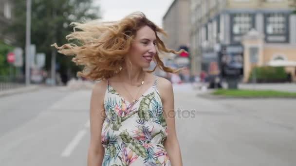 schöne junge blonde Frau, die durch die Stadt läuft. Zeitlupe