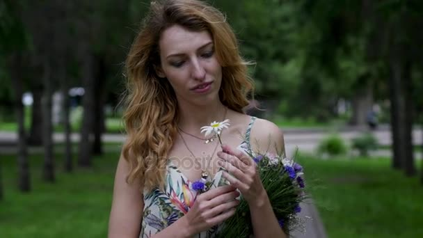 young woman with bouquet of flowers walking in the park