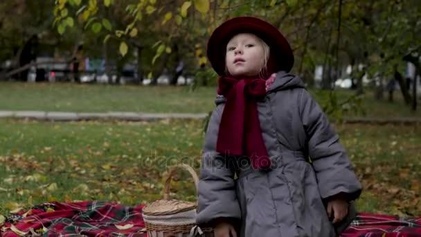 kislány játszó a parkban, levelek gyűjtése a levelek egy kosár, spinning, és játszik a