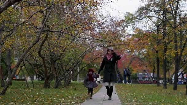 Mladá žena s dcerou procházky po parku, hraní a běhání po uličce