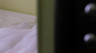 The wedding dress is on the bed. slow motion