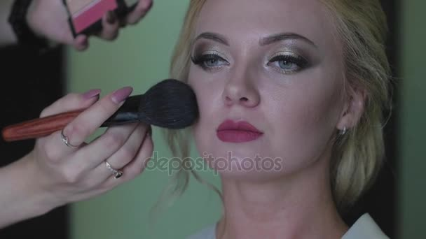 bride doing makeup before the wedding. a young woman takes a stylist