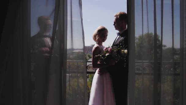 the bride and groom standing on the balcony waiting for the wedding