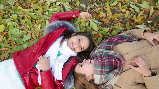 two young women lying in the Park on autumn leaves. outdoors