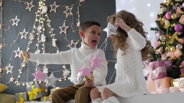 Kinder spielen in einer Girlande auf dem Hintergrund eines Weihnachts-Interieurs. New Years Studio