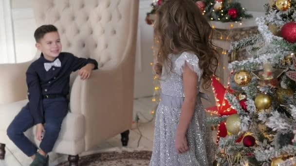 78afdb9071 Niño y niña en un interior de Navidad. el niño está sentado en la butaca