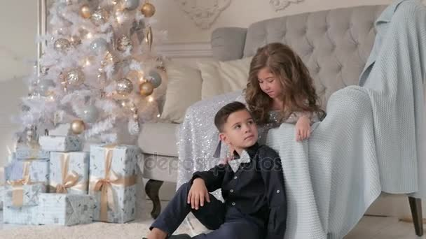 boy and girl in a christmas interior. the boy is sitting on the sofa, the girl is sitting on the couch and hugging the boy.