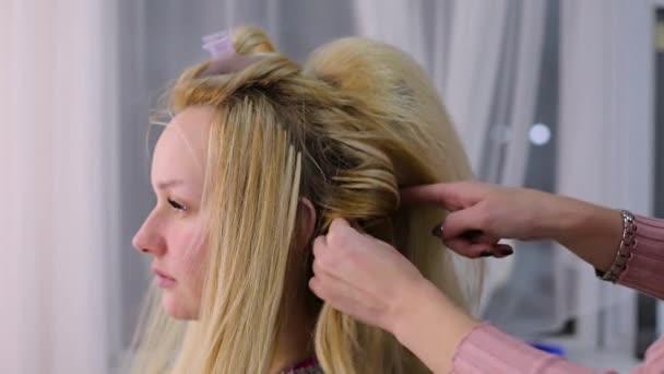 kadeřnice v salónu je klienti vlasy. blond klient s dlouhými vlasy