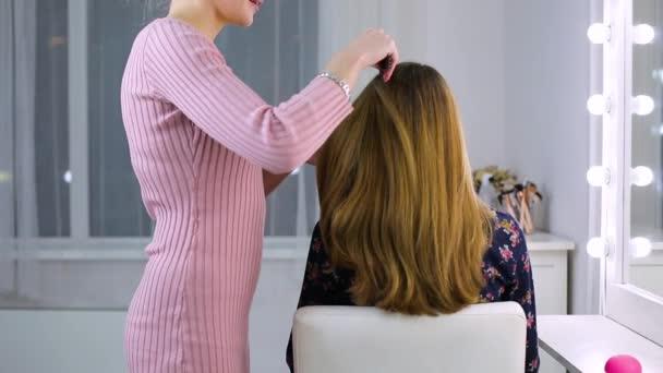 Cabeleireiro no salão faz os clientes de cabelo. garota fazendo o cabelo para  a ocasião c1a0c0b8f2