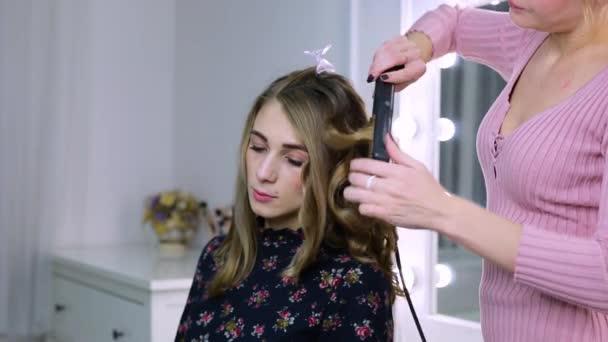 kadeřnice v salónu je klienti vlasy. holka dělá vlasy pro příležitost