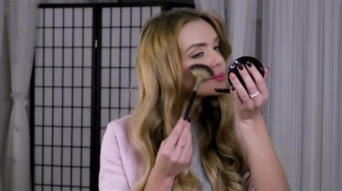 young woman applying makeup with a brush in front of a mirror