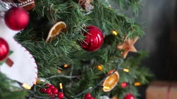 Zavřete vánoční stromeček světla třpytící se v noci. Novoroční jedle s dekoracemi a osvětlením. Vánoční stromeček dekorace pozadí. Mnoho velkých zlatých kuliček na jedli Nový rok a Vánoce