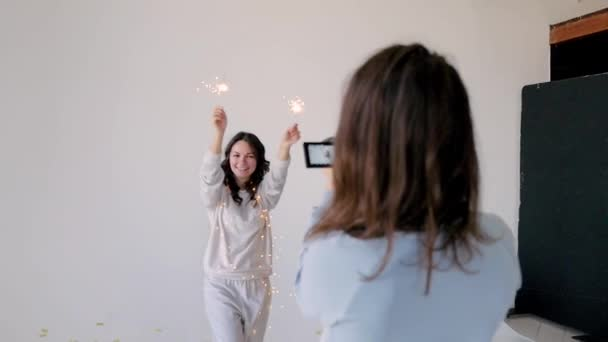 Attractive girl with sparklers with hands to camera photographer. Festive atmosphere. Christmas mood