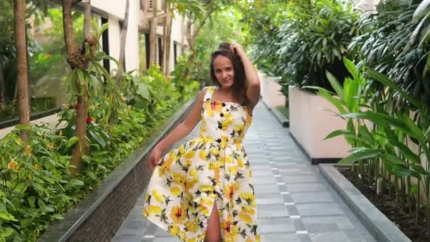 Young attractive woman in a yellow dress is dancing in a park. Girl enjoys life in the tropics on vacation