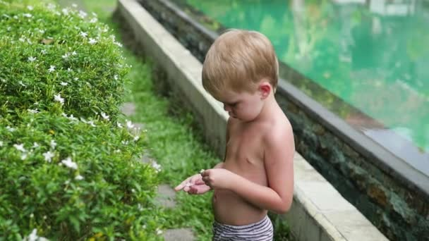Ein Kind spielt im tropischen Regen in der Nähe des Pools vor Ort. Kleiner Junge im tropischen Grün