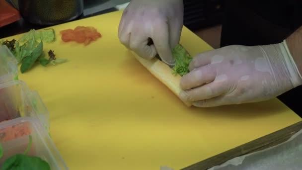 Rukou kuchaři připravují hot dog